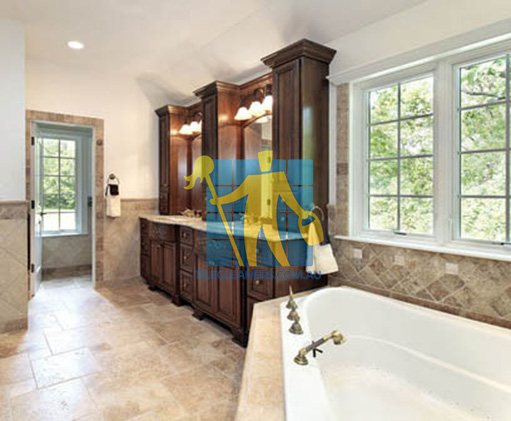 traditional bathroom with stone like tiles on floors and walls and bathtub